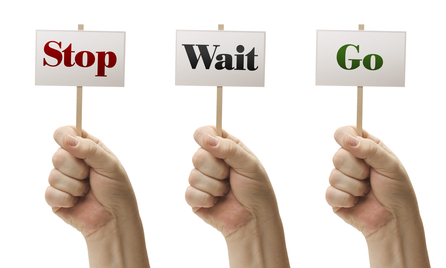 Three Signs In Male Fists Saying Stop, Wait and Go Isolated on a White Background.